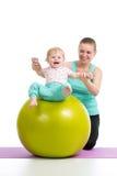 Modern med behandla som ett barn att göra som är gymnastiskt på konditionboll Royaltyfri Bild