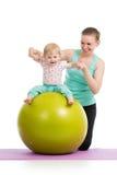 Modern med behandla som ett barn att göra som är gymnastiskt på konditionboll Royaltyfri Fotografi
