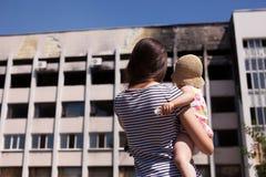 Modern med behandla som ett barn att se på bränd byggnad av det Mariuopl stadshuset Arkivfoto