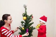Modern med behandla som ett barn dekorera julgranen Royaltyfri Foto