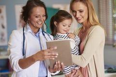 Modern med behandla som ett barn flickan på doktorns kontor Arkivbilder