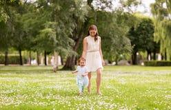 Modern med behandla som ett barn flickan som går på sommar, parkerar royaltyfria foton