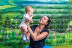 Modern med behandla som ett barn göra gymnastik Fotografering för Bildbyråer