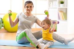 Modern med behandla som ett barn göra gymnastik, och kondition övar Fotografering för Bildbyråer