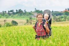 Modern med behandla som ett barn i bärande ryggsäck som går på risterrasser Royaltyfri Foto