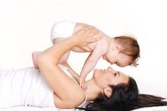 Modern med behandla som ett barn isolerat på vit. Lycklig familj med nyfött. Arkivfoto