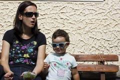 Modern med behandla som ett barn på en bänk royaltyfria bilder
