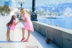 Modern med den lilla charmiga dottern sitter i staden i solljus modern matar hennes dotter och talar till henne med royaltyfri bild