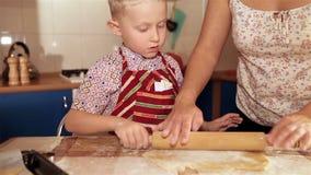 Modern med den lilla sonen knådar en deg för pepparkakan lager videofilmer