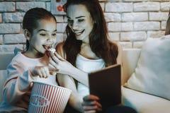 Modern med dottern använder en minnestavlaPC fotografering för bildbyråer