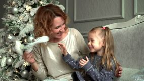 Modern med dottern på en julgran sitter på en soffa och ett skratt Modern killar den blonda dottern en vit stock video
