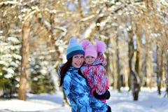Modern med dottern på går lite i träna på en snöig vinter royaltyfri fotografi