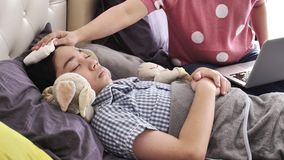 Modern med ett barn försöker att arbeta på bärbar datordatoren hemma, en sjuk pojke låg i säng stock video