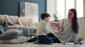 Modern med ett barn i den vita inre av hans hus öppnades målarfärgen kan sammanträde på golvet och att doppa ditt arkivfilmer