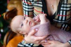 Modern med förälskelse- och mjukhethåll på händer av det nyfött behandla som ett barn, ungen med kuriositetblickar i kameran Mode arkivbild