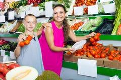 Modern med flickan som väljer mogna tomater shoppar in Arkivfoto