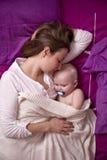Modern med henne behandla som ett barn att sova i säng Arkivbild