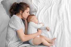 Modern med henne behandla som ett barn att sova på säng royaltyfria foton