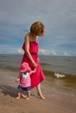 Modern med henne behandla som ett barn ha gyckel på stranden arkivfoton