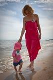 Modern med henne behandla som ett barn ha gyckel på stranden royaltyfria bilder