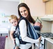 Modern med hennes barn i rem och behandla som ett barn bäraren arkivbilder