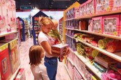 Modern med hennes döttrar väljer en docka i en leksak shoppar Arkivfoton