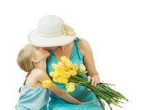 Modern med hennes dotter i blått klär med en bukett av tulpan som isoleras på vit bakgrund Royaltyfria Bilder