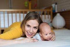 Modern med hennes nyfött behandla som ett barn sonen som ligger på säng royaltyfri bild