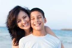 Modern med hennes son har gyckel på stranden royaltyfria foton