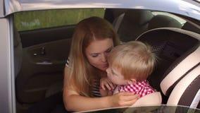 Modern med hennes son i bilen, pojken bär en säkerhetsbälte i bilsätet arkivfilmer