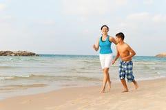 Modern med hennes son kör på stranden arkivbild