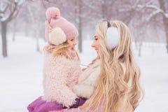 Modern med lång blond krullning kramar hennes härliga lilla dotter i en rosa hatt med en bubo royaltyfria bilder