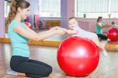 Modern med lyckligt behandla som ett barn göra övningar med den gymnastiska bollen Royaltyfri Bild
