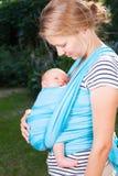 Modern med nyfött behandla som ett barn i rem arkivbilder