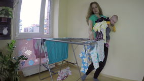 Modern med nyfött behandla som ett barn på hennes händer väljer upp den torra tvätterit 4K lager videofilmer