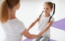 Modern med praktiserande yoga för barn i lotusblomma poserar royaltyfria bilder