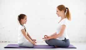 Modern med praktiserande yoga för barn i lotusblomma poserar royaltyfri bild