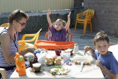 Modern med söner har frukosten Arkivfoto