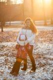 Modern med sex åriga dotteranseende i vinter parkerar under strålarna av inställningssolen Arkivfoton