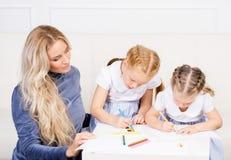 Modern med två härliga döttrar drar Royaltyfri Fotografi