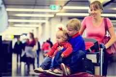 Modern med två ungar reser i flygplatsen arkivbild