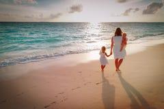 Modern med ungar går på sandstranden arkivfoton