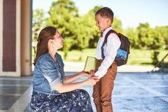 Modern medföljer barnet till skola mamman uppmuntrar studenten som medföljer honom till skola en att bry sig moder ser ömt på hen royaltyfri bild