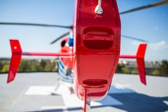 Modern medical helicopter on a hospital rooftop helipad from behind stock images