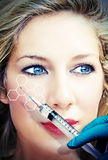 Modern medical research. Face of a beautiful woman with doctors hand and syringe stock photos