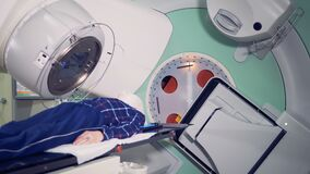 Modern medicine concept. Patient lying on a table while a linear accelerator is treating him. Side view of a patient lying on a table while a linear accelerator stock footage