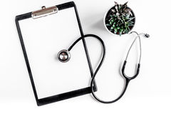 Modern medicine workplace with board, stethoscope white table flat lay space for text Royalty Free Stock Photo
