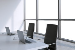 Modern meeting room with huge windows with copy space. Black leather chairs and a white table with laptops. Royalty Free Stock Images