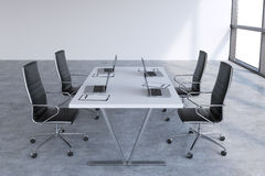 Modern meeting room with huge windows with copy space. Black leather chairs and a white table with laptops. Stock Photos