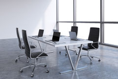 Modern meeting room with huge windows with copy space. Black leather chairs and a white table with laptops. Stock Images